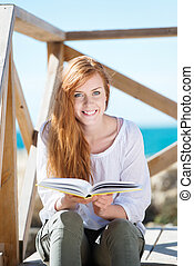 Smiling woman reading at the seaside