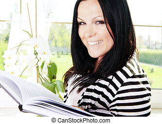 woman reading book in house