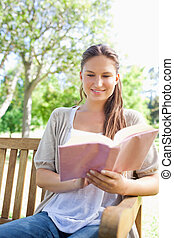 Smiling woman reading her book on a park bench