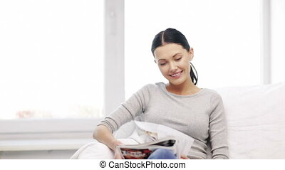 smiling woman reading magazine at home - homa and leasure...