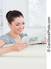 Smiling woman reading the news while sitting on a couch