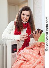 smiling woman reads eBook near warm radiator in home