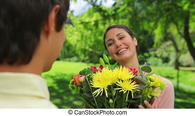 Smiling woman receiving a bunch of flowers