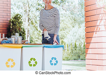 Smiling woman recycling waste