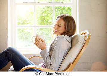 Smiling woman relaxing at home with cup of tea