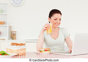 Smiling woman relaxing on her laptop and posing while drinking a glass of orange juice in her kitchen