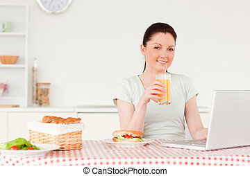 Smiling woman relaxing on her laptop while drinking a glass of orange juice in her kitchen
