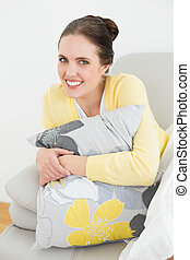 Smiling woman relaxing on sofa at home