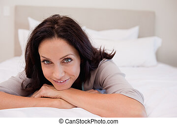 Smiling woman relaxing on the bed