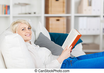 smiling woman relaxing with a book