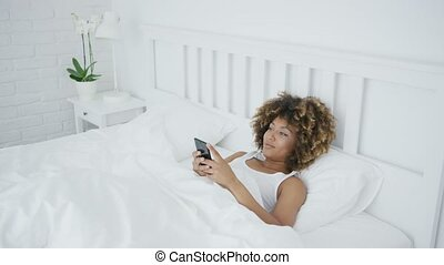 Smiling woman relaxing with phone in bed - Pretty happy...