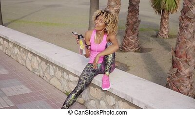 Smiling woman resting from workout at beach