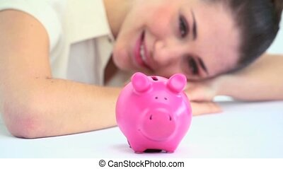 Smiling woman resting on a table with a piggy bank
