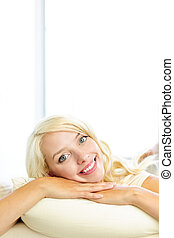 Smiling woman resting on cushion