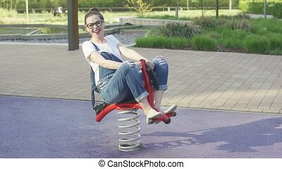 Smiling woman riding spring toy on playground