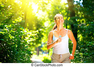 Smiling woman running outdoor over sunrise. Brunette model jogging in the park