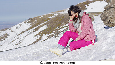 Smiling woman sat on snowy mountain summit