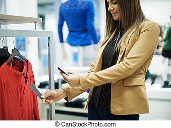 Smiling woman scanning QR code on smart phone