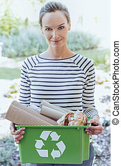 Smiling woman segregating paper junk - Smiling aware woman ...
