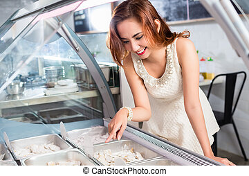 Smiling woman selecting food from a deli counter