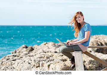 Smiling woman sending emails at the seaside sitting on a...