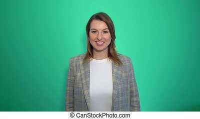Smiling woman sends air kiss at the camera over green background