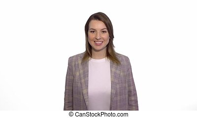 Smiling woman sends air kiss at the camera over white background