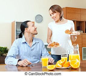 Smiling woman serves breakfast her  husband