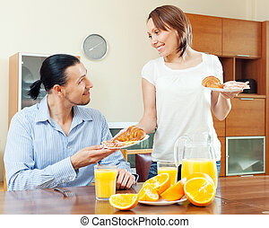 Smiling woman serves croissants and scrambled eggs her  man