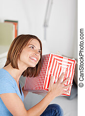 Smiling woman shaking her gift