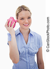 Smiling woman shaking her piggy bank