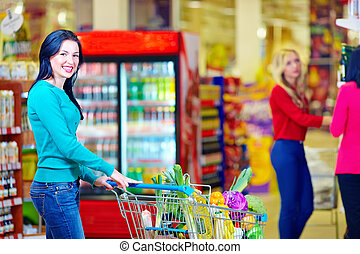 smiling woman shopping at supermarket with trolley