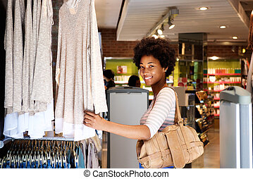 Smiling woman shopping in clothing store