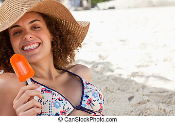 Smiling woman showing a beaming smile while holding a delicious orange popsicle