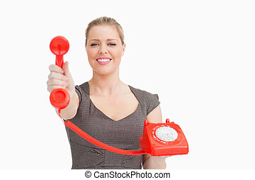 Smiling woman showing a retro phone