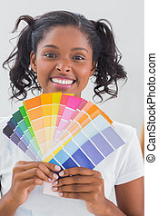 Smiling woman showing colour charts