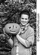 smiling woman showing Halloween pumpkin Jack O'Lantern