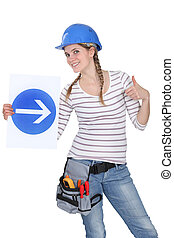 Smiling woman showing road sign