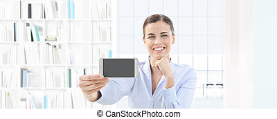 smiling woman showing smartphone in her hand on interior office background