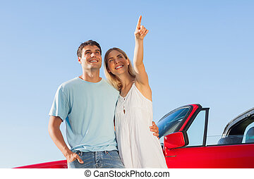 Smiling woman showing something to her handsome boyfriend