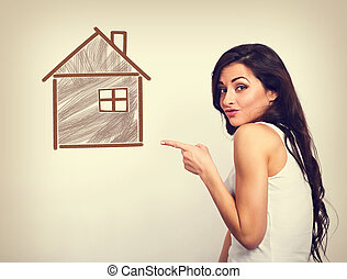 Smiling woman showing the hand on small illustration wooden house. Insurance protection concept or investment to safety money. Vintage color style