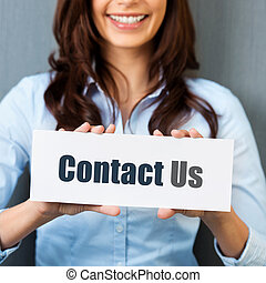 Contact us - Smiling woman showing white card with Contact...
