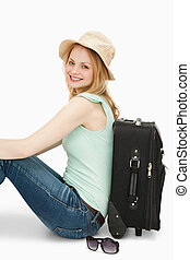 Smiling woman sitting against a suitcase
