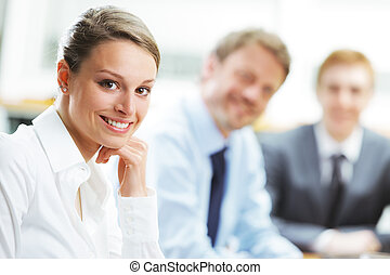 Smiling woman sitting at a business meeting with colleagues