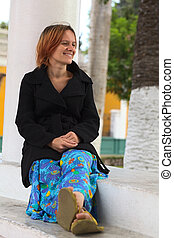 Smiling Woman Sitting at a Column