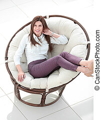 smiling woman sitting in comfortable round chair