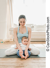 Smiling woman sitting in lotus position with her little child