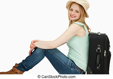Smiling woman sitting near a suitcase
