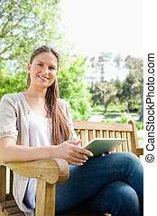 Smiling woman sitting on a bench with her tablet computer