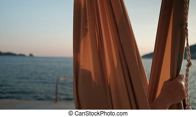Smiling woman sitting on a hammock by the lake at sunset.